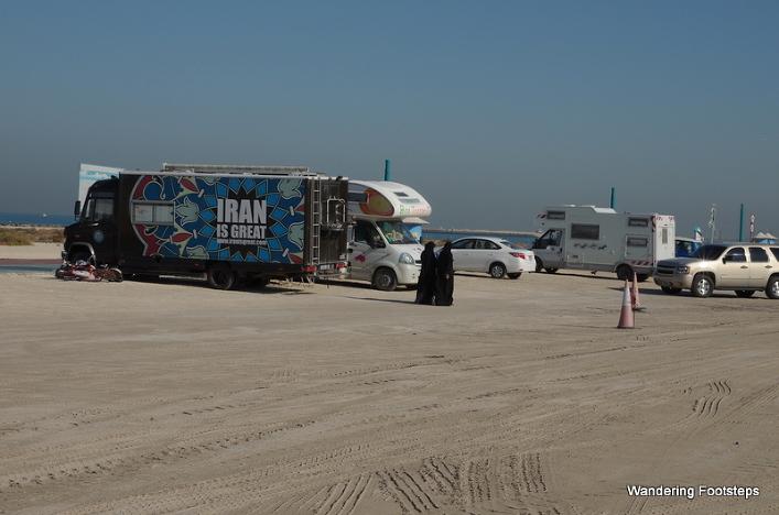 Overlanders parked along a public beach in Dubai.