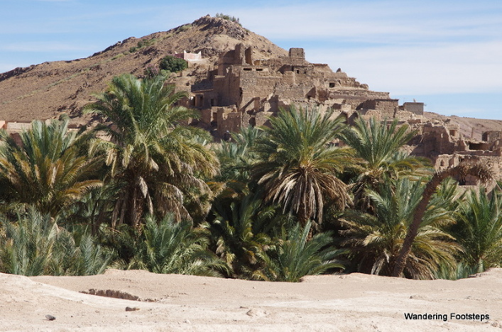 A barely-visible town in a palmeraie after kilometers of empty hammada.